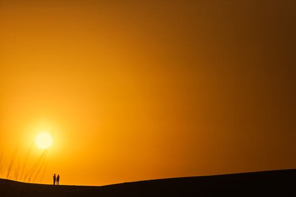 A couple having view of a sunset at sand dunes, Jaisalmer.